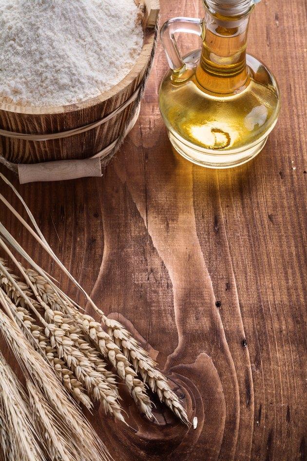ears of wheat wooden bucket flour oil bottle on vintage