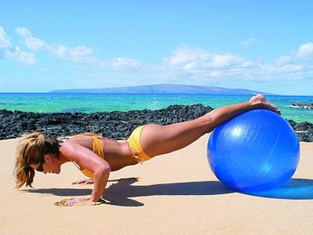 Photo, woman wearing a swimsuit working out with a large blue ball on the beach, Color, High res