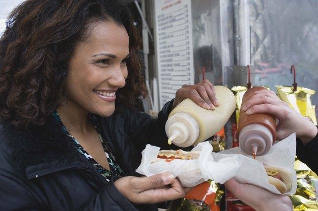 Woman with hot dog at vending cart