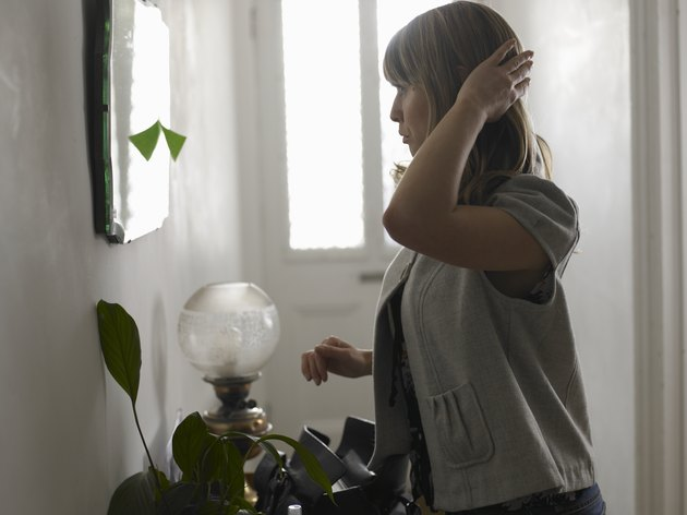 Young woman checking appearance in hall mirror, side view