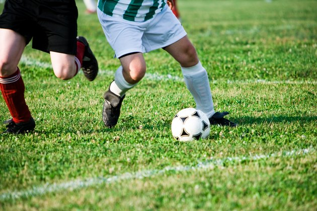 Two soccer players competing for ball