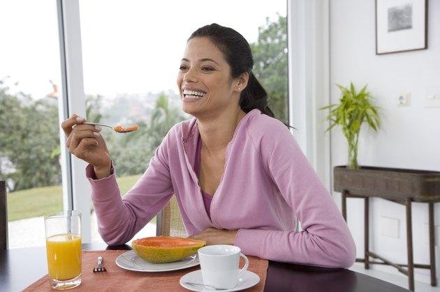Close-up of young woman eating papaya