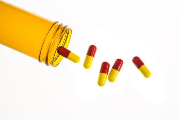 Jar of medicine spilling capsule tablets