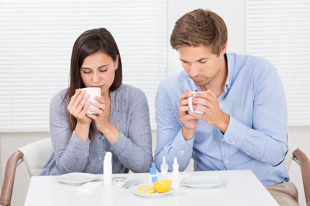 Sick Couple Drinking Lemon Tea At Table