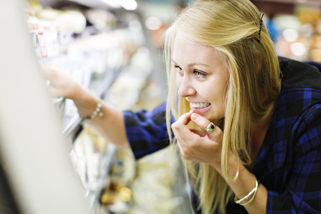 Beautiful blonde shopper checks supermarket fridge contents, smiling