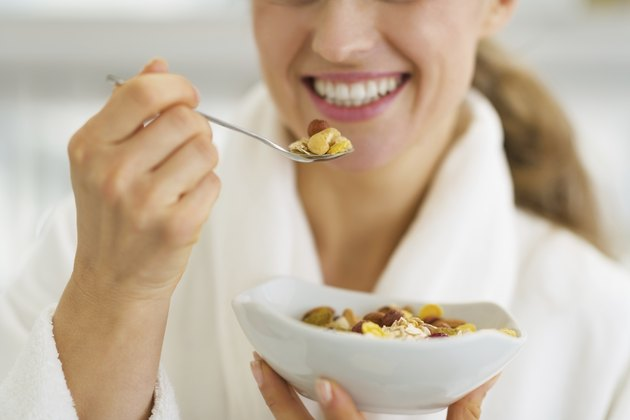 closeup on happy woman in bathrobe having healthy breakfast