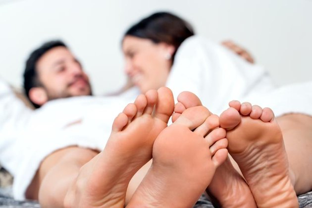 Close up detail of human feet together with out of focus laughing couple in background.