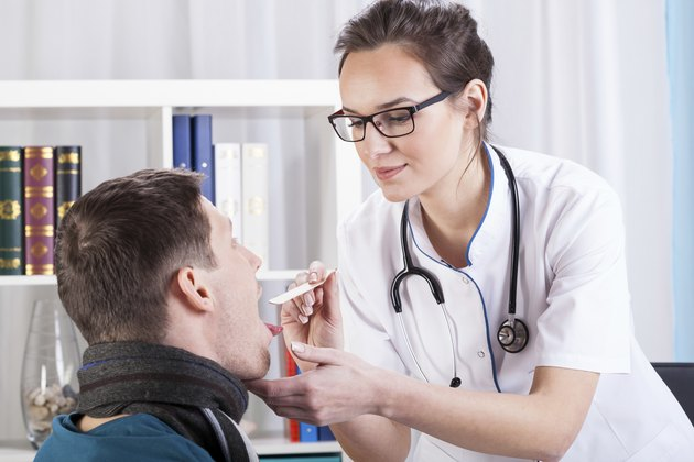 Doctor examining patient with sore throat