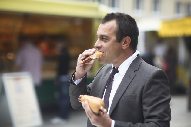 Businessman eating hotdog outside