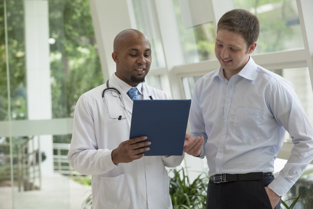 Doctor and patient looking down and discussing medical record in the hospital