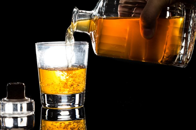 Hand pouring whiskey into glass against dark background