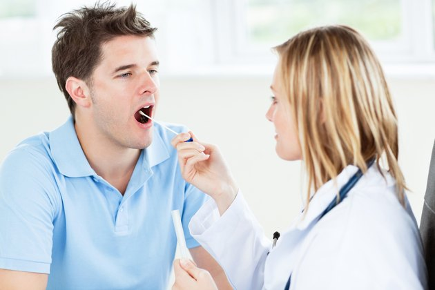 Caucasian female doctor taking a saliva sample of a male patient using cotton-bud
