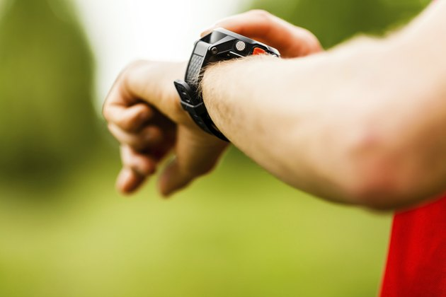 Cross country trail runner looking at sport watch