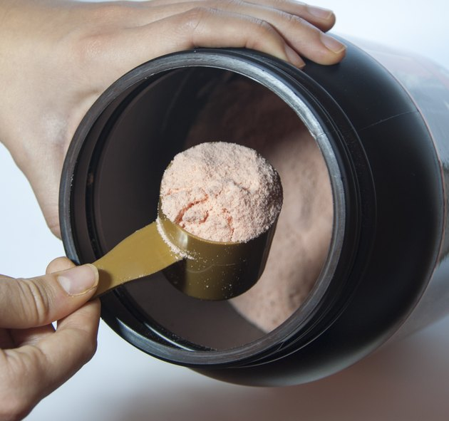 Man taking scoop of protein from black container