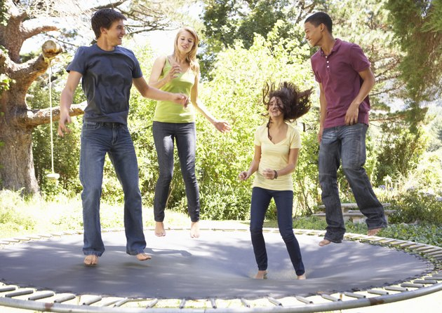 Four Teenage Friends Jumping On Trampoline In Garden