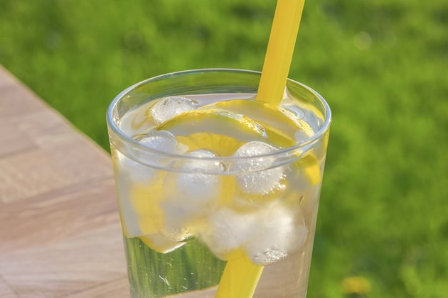 Glass of ice water with lemon slices and straw