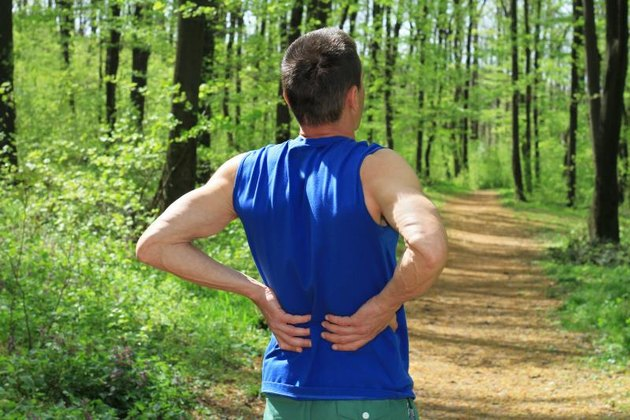 Back pain. Man Runner lower back pain injury