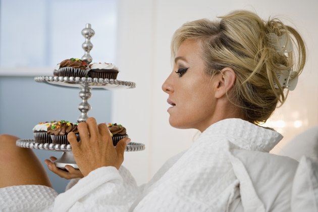 Mature woman eating cupcakes in bed