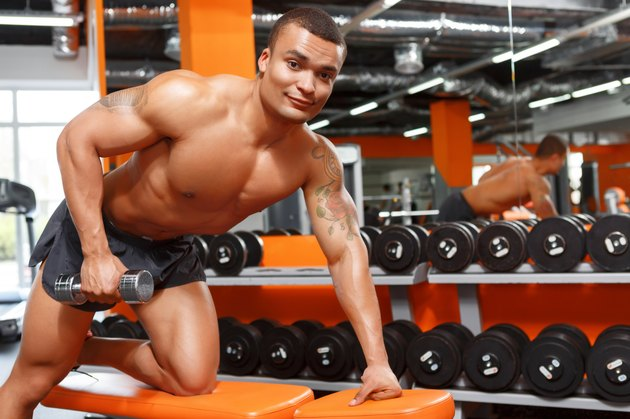 Muscular man doing exercises with dumbbells in gym