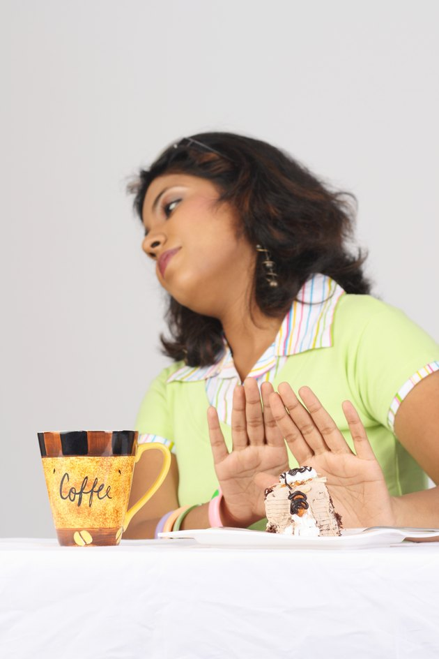 A girl refusing to eat a pastry
