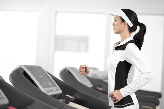 Young Woman Fitness Model Running Jogging on Treadmill in Gym