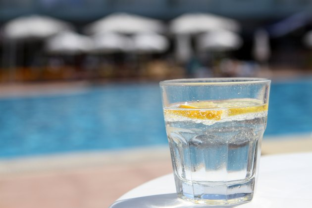Fresh water with lemon cocktail near pool on the table
