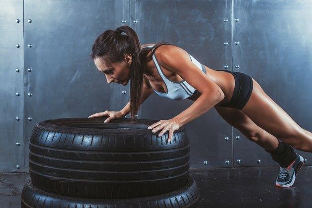 Sportswoman. Fit sporty woman doing push ups on tire strength