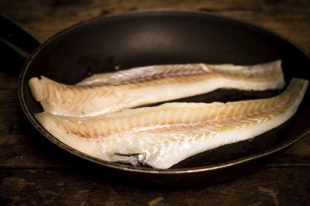 Two haddock fillets in frying pan