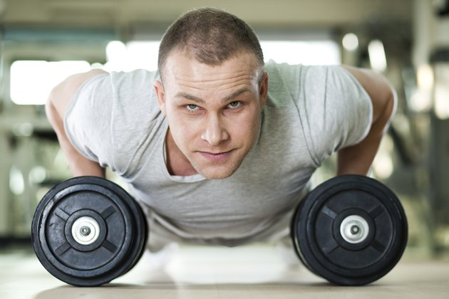 Young man doing push-ups on dumbbells.