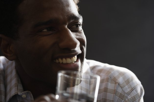 Close-up of a mid adult man holding a glass of water smiling