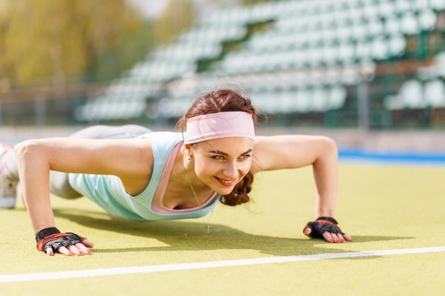 Young attractive woman doing push-up or core exercise on the grass field
