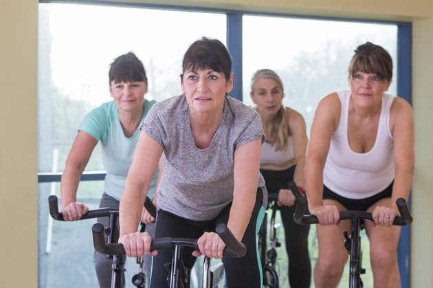 Senior women using spinning bikes