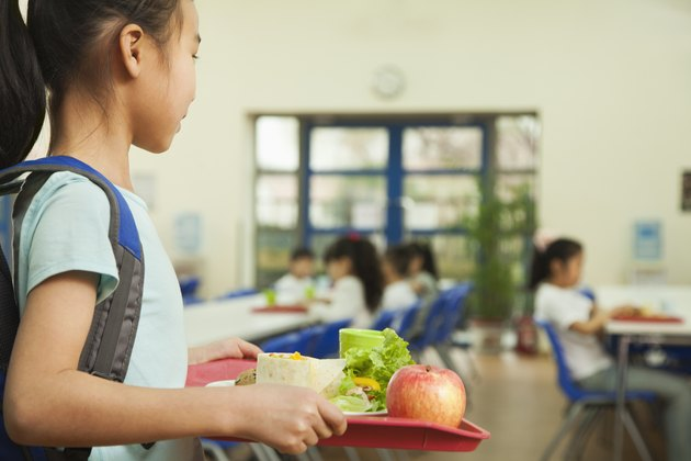 School girl holding food tray in school cafeteria