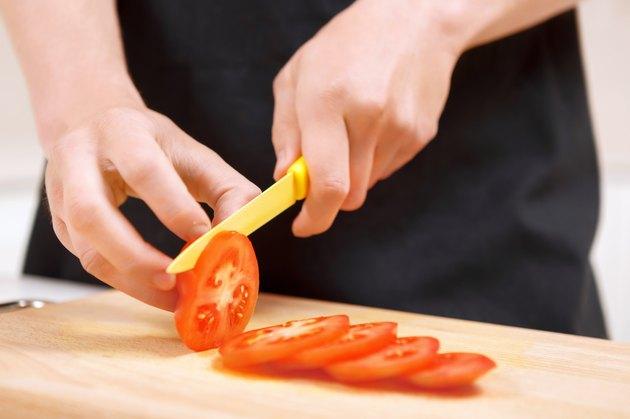 Close up of man slicing tomatoes