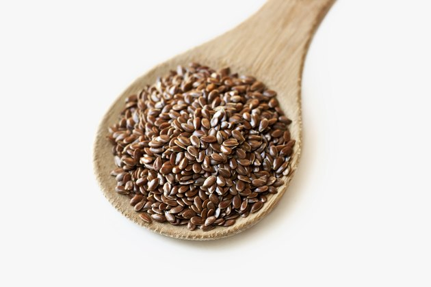 Spoonful of flax seeds isolated on white