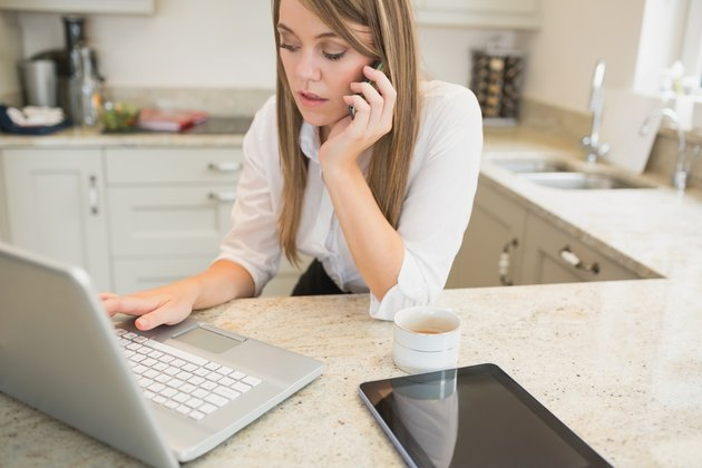 Stressed woman on phone and laptop