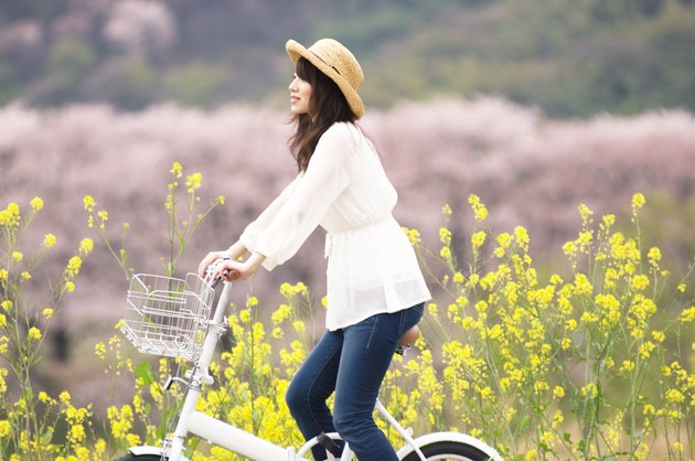 Woman cycling through spring landscape