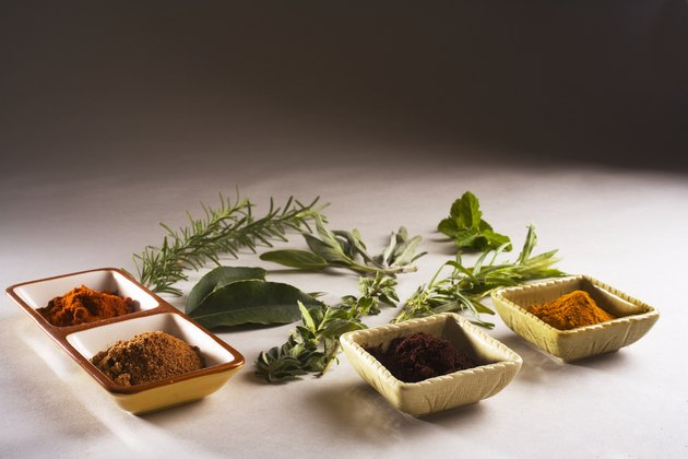 Barbecue scene, fresh herbs and spices laid out on white background.