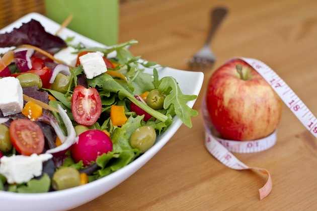 Healthy green salad and an apple with measuring tape