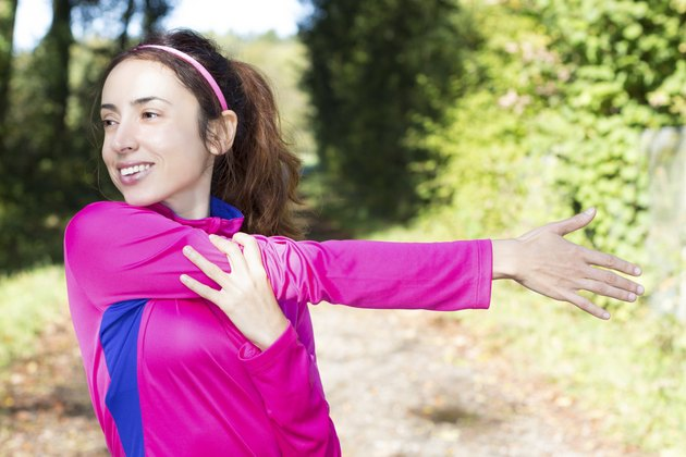 Sporty woman stretching her arm in forest