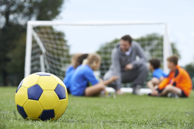 Coach  And Team Discussing Soccer Tactics With Ball In Foregroun
