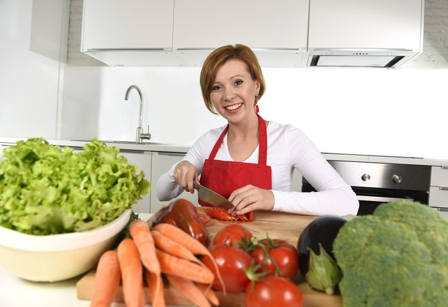 happy young woman at home kitchen preparing vegetable salad