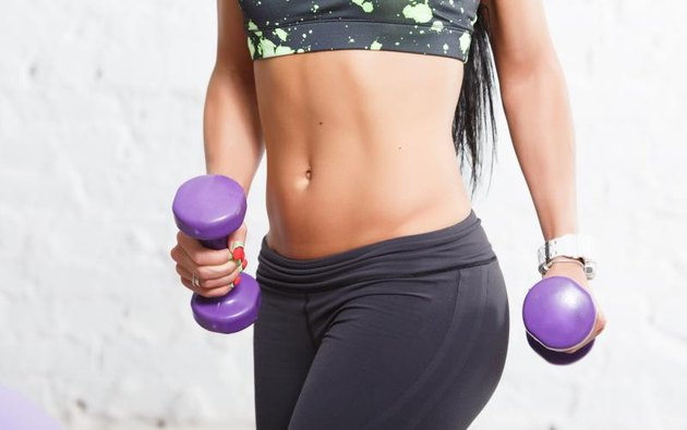 Close up athletic young woman showing some strong abs and flat belly, in sports outfits with beautiful body, holding purple dumbbells, against concrete wall