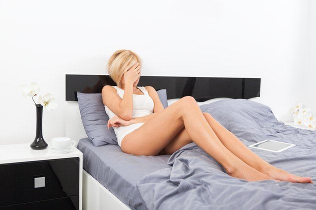 upset woman covering her face hand lying on bed
