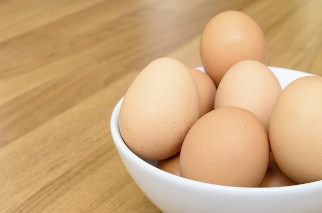 Eggs in white bowl on wooden table