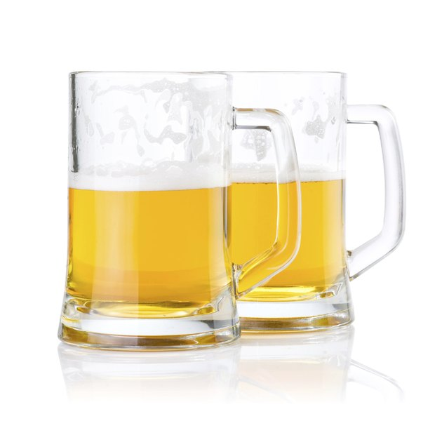 Two half glasses of fresh beer with foam isolated