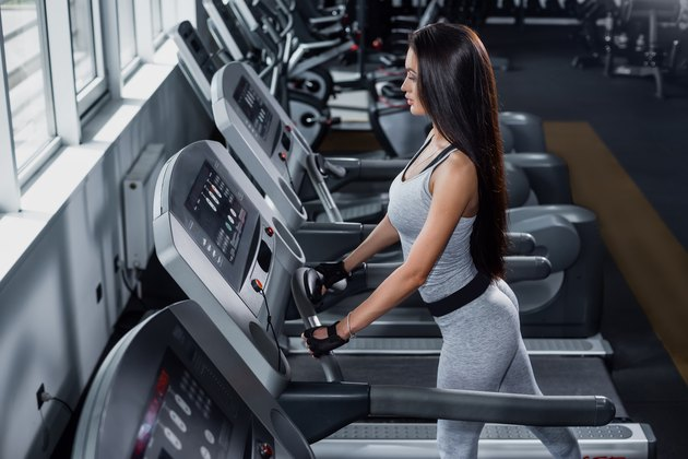 Training in the gym. Fitness girl burn calories on the treadmill. Fitness trainer doing cardio workout. Workout on the treadmill