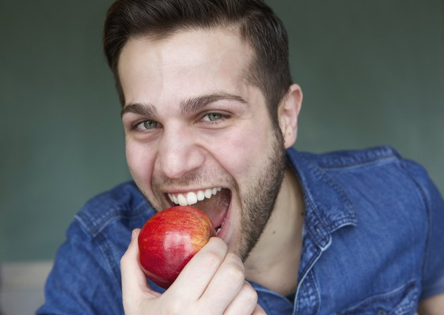 Healthy young man eating apple