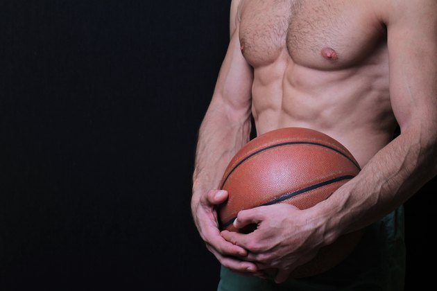 Close up of muscular man holding a basketball.