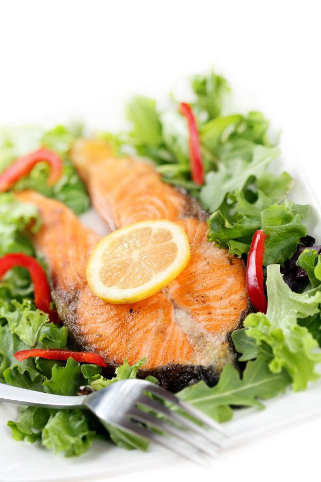 fried salmon with salad isolated